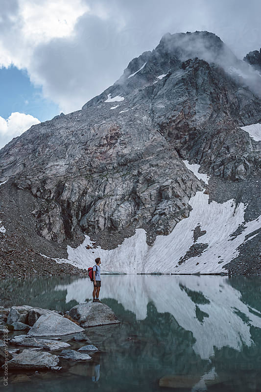 Man standing on a lake in mountain by GIC for Stocksy United