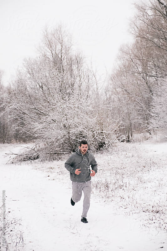 Bearded man running in winter forest under snowfall by Danil Nevsky for Stocksy United