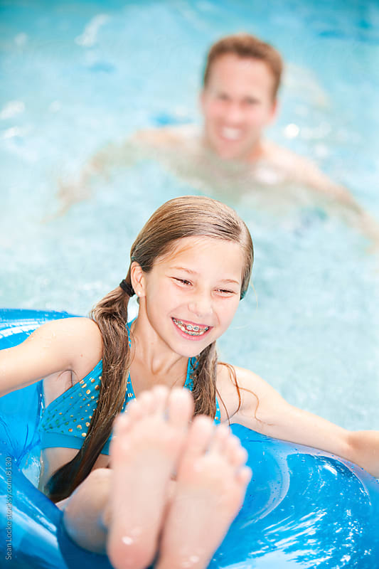 Swimming: Girl Playing with Dad in Pool by Sean Locke for Stocksy United