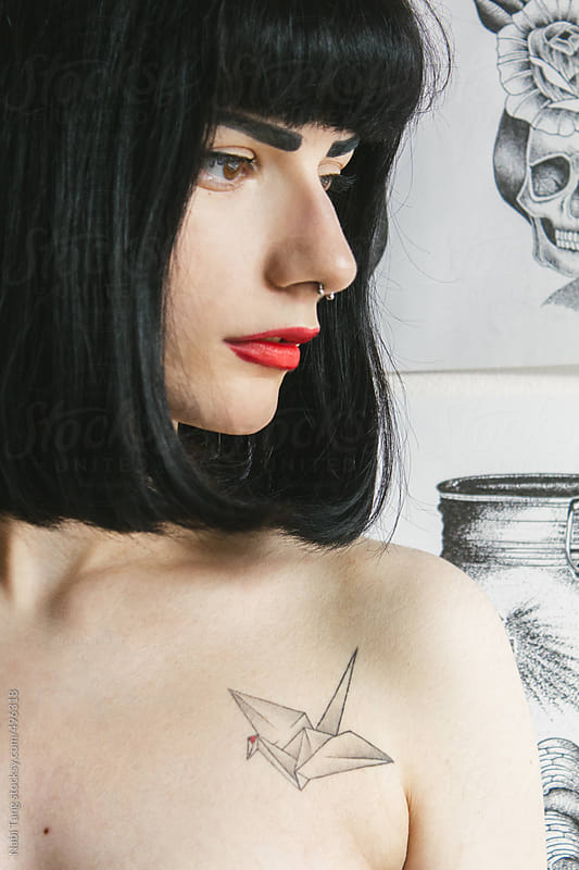 Beautiful young woman with illustration art work on the white wall by Nabi Tang for Stocksy United