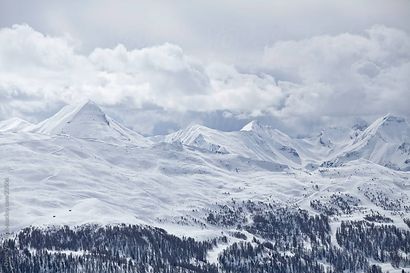 Snowy mountain tops in the cold by Denni Van Huis for Stocksy United