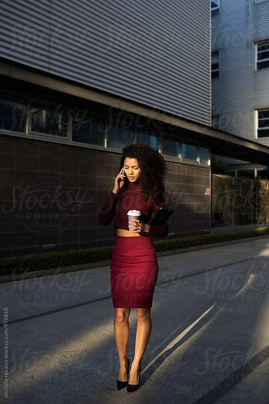 Business woman talking on cell phone holding a coffee mug by michela ravasio for Stocksy United