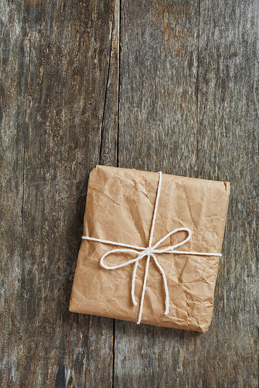 Package wrapped in wrinkled brown paper lying on weathered wood by David Smart for Stocksy United