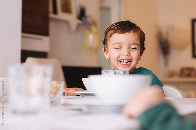 Happy kid sitting on a table ready for lunch. by BONNINSTUDIO for Stocksy United