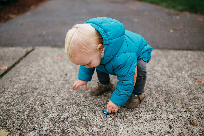 Little Boy In Bright Blue Winter coat Plays with a Car on the driveway by Amanda Voelker for Stocksy United