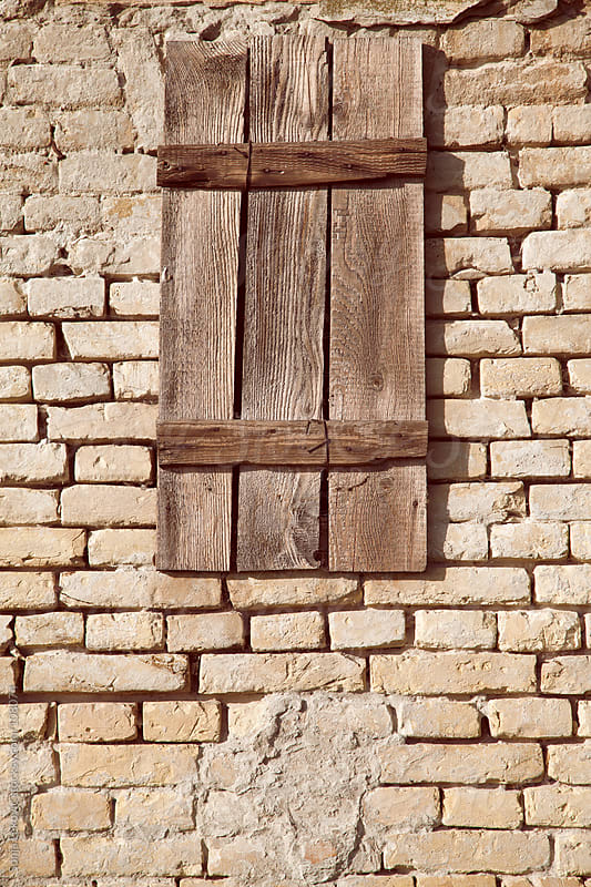 closed wooden window on a brick wall by Sonja Lekovic for Stocksy United