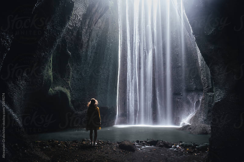 woman looking at the waterfall at cave by Alexander Grabchilev for Stocksy United
