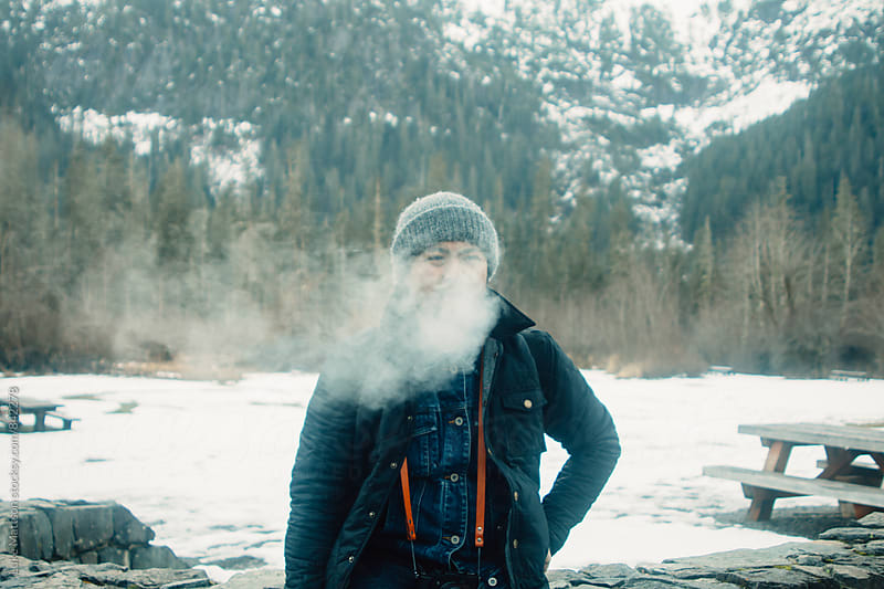 Cloud Of Cigarette Smoke Covering Young Man's Face Who Is Standing Outside In Snow by Luke Mattson for Stocksy United