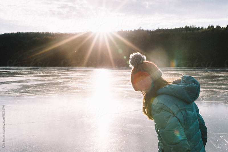 young woman on lake with sunshine by Léa Jones for Stocksy United