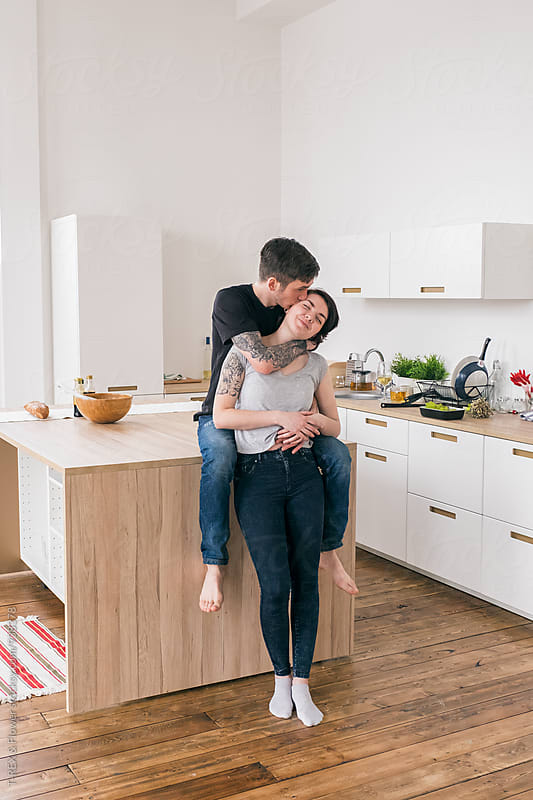 Couple kissing in the kitchen by Danil Nevsky for Stocksy United