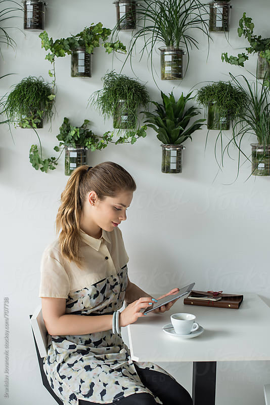 Young Businesswoman Sitting at the Cafe and Using Tablet Computer by Branislav Jovanović for Stocksy United
