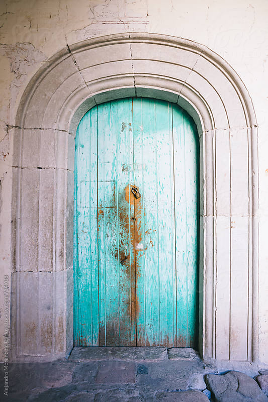 Turquoise wooden door in a church by Alejandro Moreno de Carlos for Stocksy United