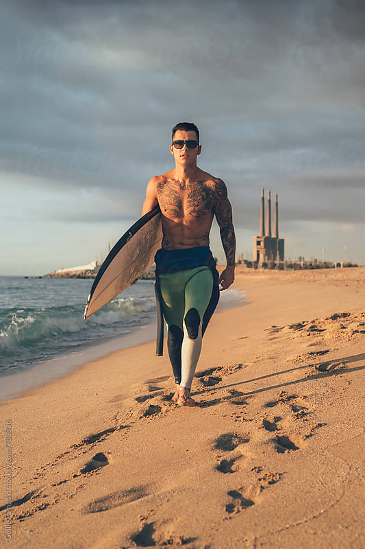 surfer walking on the shore by Guille Faingold for Stocksy United