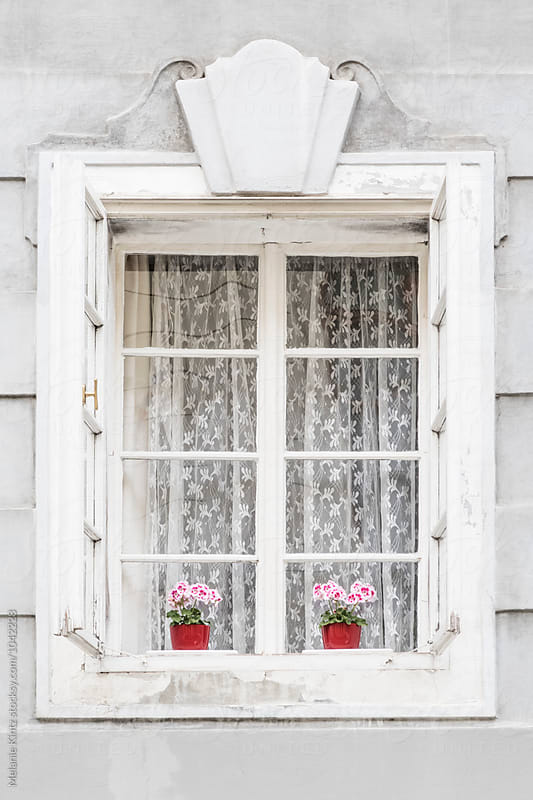 Historic window with geraniums in red pots by Melanie Kintz for Stocksy United