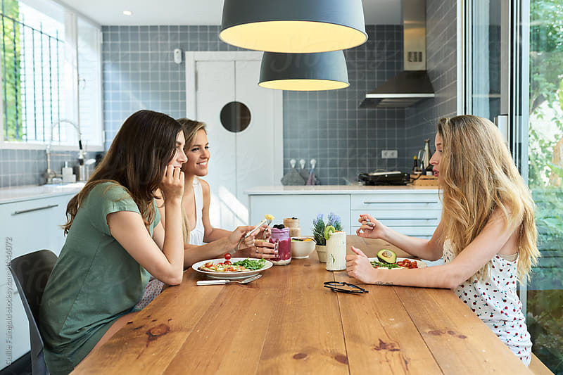 Side view of three friends having breakfast in kitchen by Guille Faingold for Stocksy United