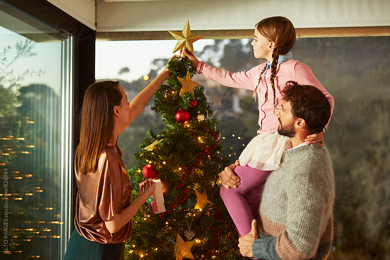 Family Putting Star On Top Of Christmas Tree At Home by ALTO IMAGES for Stocksy United