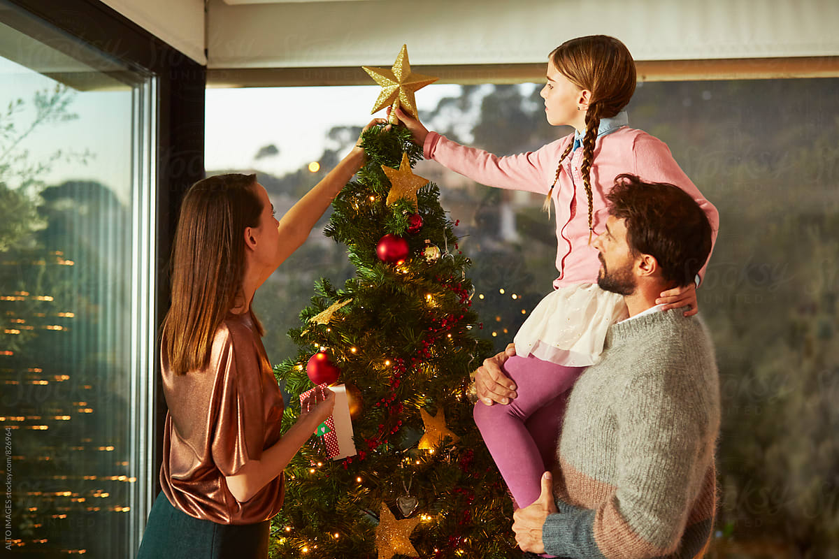 A Star For Christmas.Family Putting Star On Top Of Christmas Tree At Home By Alto
