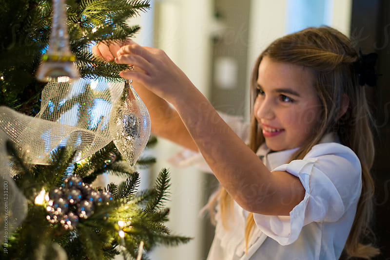 Little Girl Hanging Christmas Ornaments on Christmas Tree by JP Danko for Stocksy United