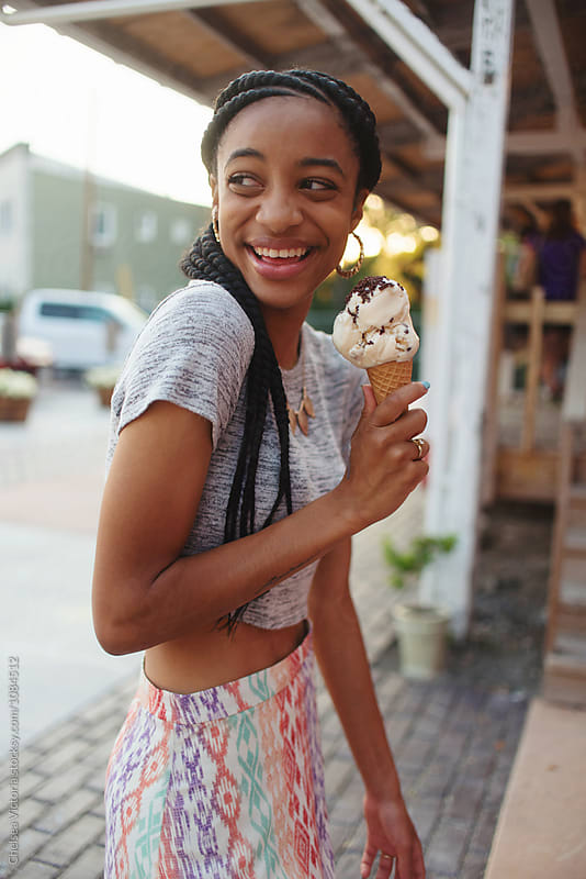 A young woman eating ice cream in the summertime by Chelsea Victoria for Stocksy United