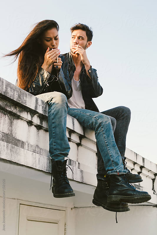 Couple sitting on a rooftop and lighting cigarette.  by Jovo Jovanovic for Stocksy United
