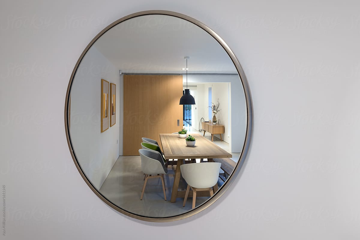 Reflection In A Mirror Of A Dining Room Illuminated At Night By Paul Phillips Stocksy United