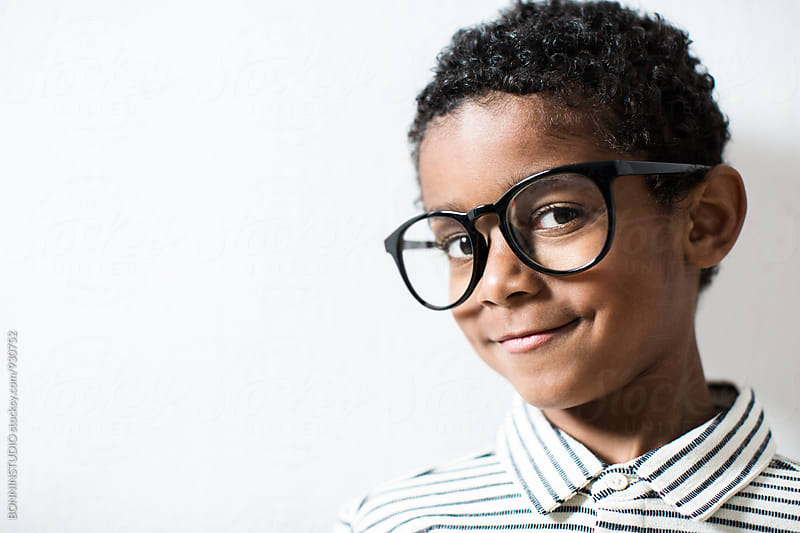 Portrait of a smiling little boy wearing a rimmed glasses. by BONNINSTUDIO for Stocksy United