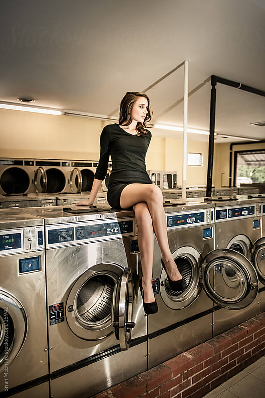 Laundromat: Woman Sitting On Washing Machine by Brian McEntire for Stocksy United