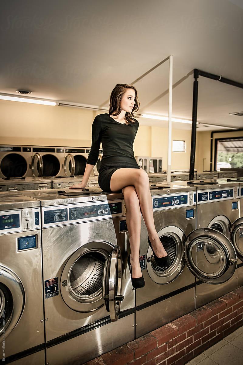 Girl sitting on washing machine