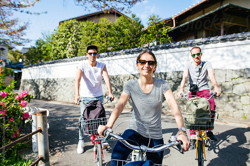 Portrait of tourist friends riding their bicycles in Kyoto. by BONNINSTUDIO for Stocksy United