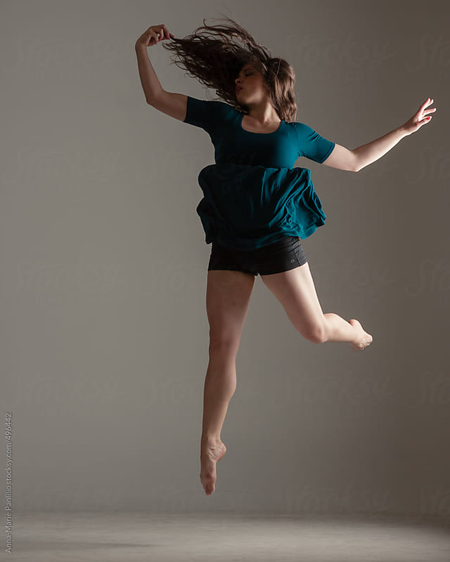 Brunette female contemporary dancer with short green dress by Anna-Marie Panlilio for Stocksy United