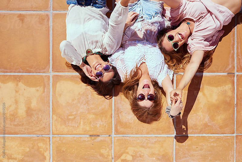 Three cheerful friends in sunglasses lying on floor by Guille Faingold for Stocksy United