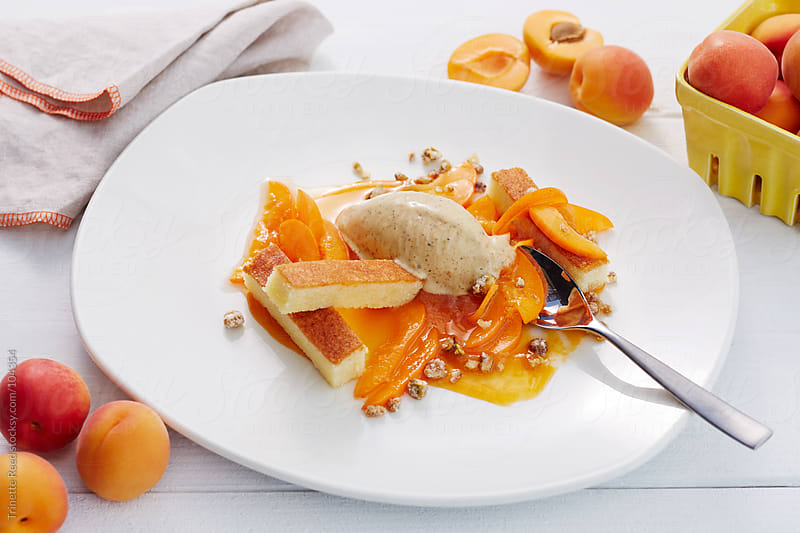 Fresh peach dessert with cake, and vanilla bean ice cream by Trinette Reed for Stocksy United