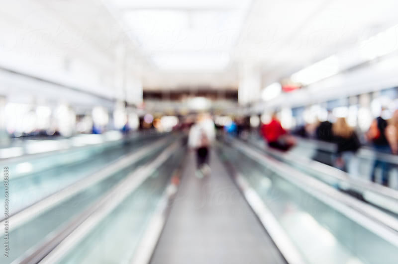 Defocused image of people on a moving walkway at an airport terminal by Angela Lumsden for Stocksy United