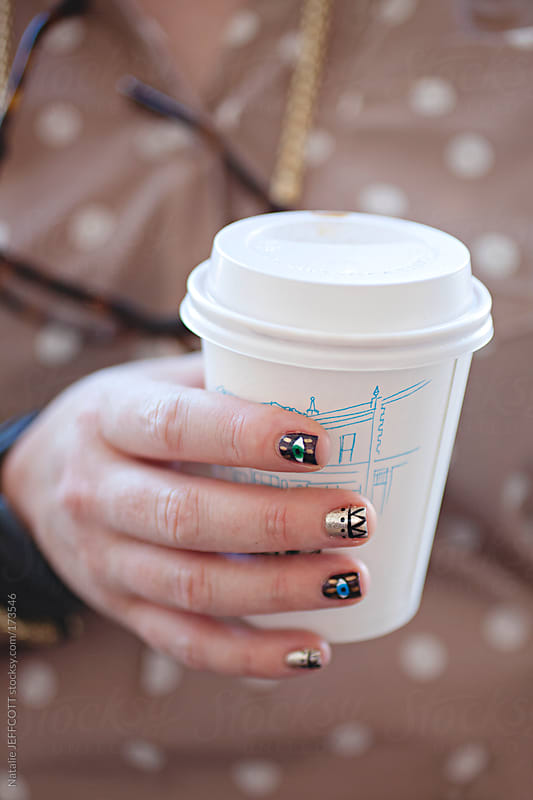 close up of hand holding take away coffee cup with fancy painted finger nails by Natalie JEFFCOTT for Stocksy United