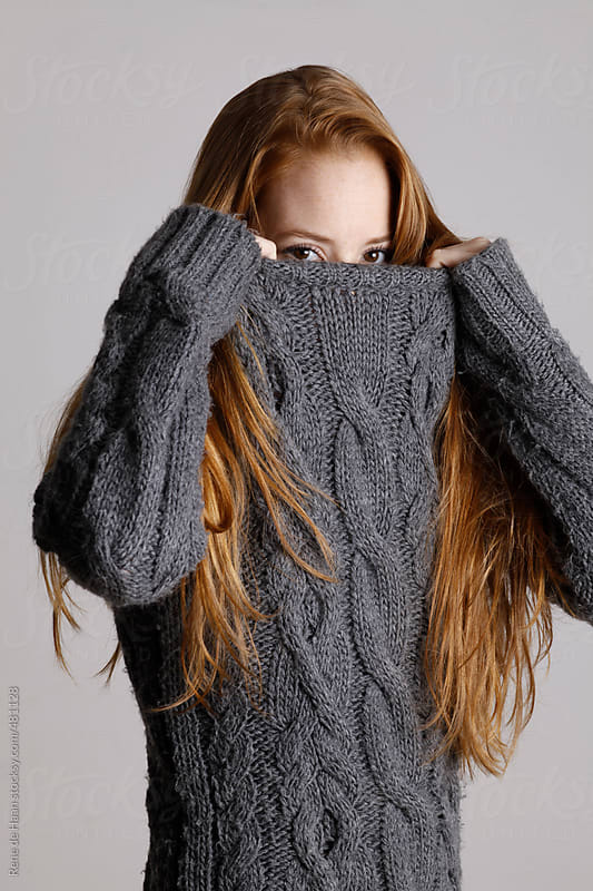 girl with long red hair  pulling sweater over her face by Rene de Haan for Stocksy United