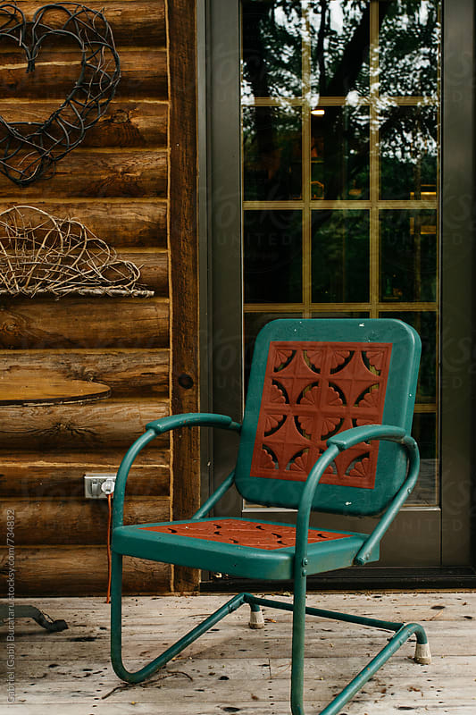 Empty chair on a log cabin porch by Gabriel (Gabi) Bucataru for Stocksy United