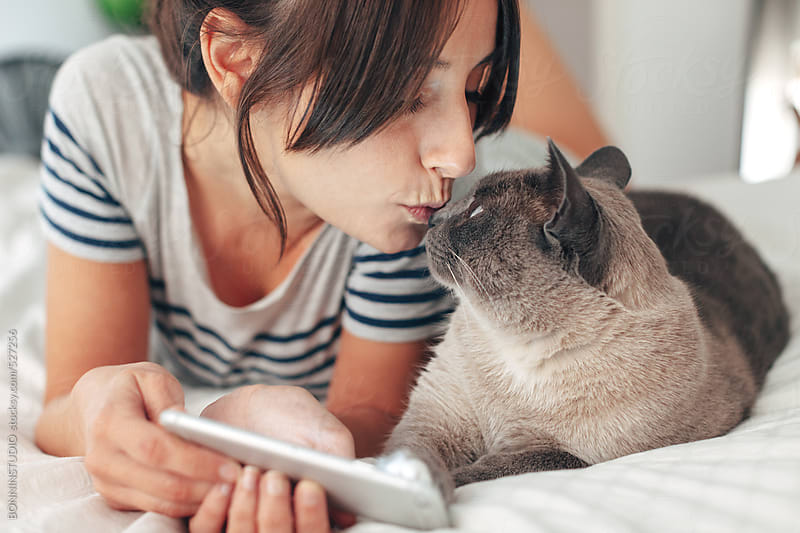 Young woman kissing her siamese cat in the bedroom.  by BONNINSTUDIO for Stocksy United