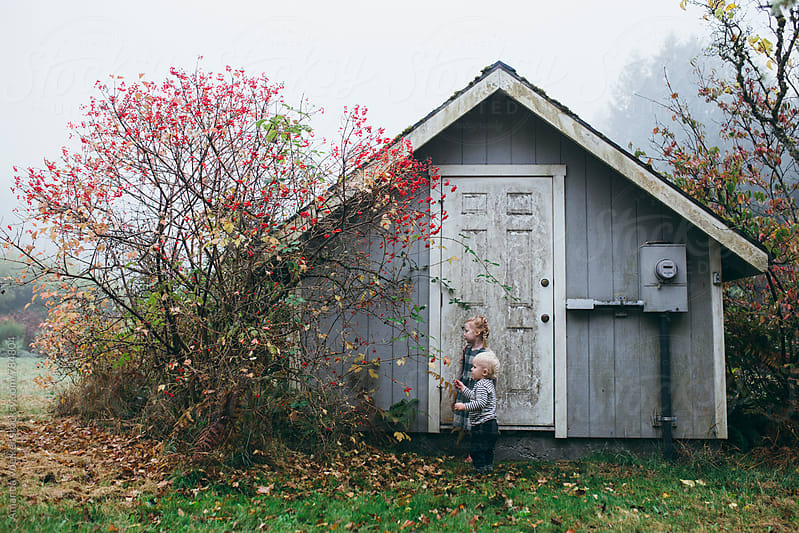 A young brother and sister stand outside a toolshead in autumn by Amanda Voelker for Stocksy United