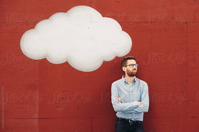 Man dreaming big ideas in his cloud on a red wall by Ania Boniecka for Stocksy United