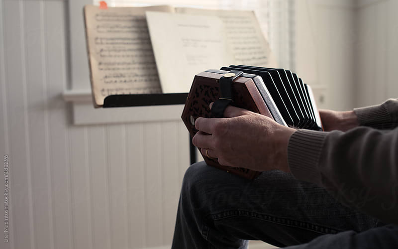 hands holding concertina in front of sheet music by Lisa MacIntosh for Stocksy United