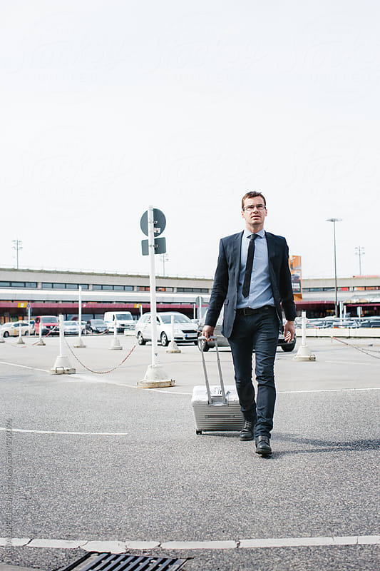 Caucasian Businessman Rushing on Airport Carpark by Julien L. Balmer for Stocksy United