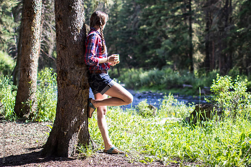A young woman leans up against a tree drinking her morning coffee by the river by Hannah Dewey for Stocksy United