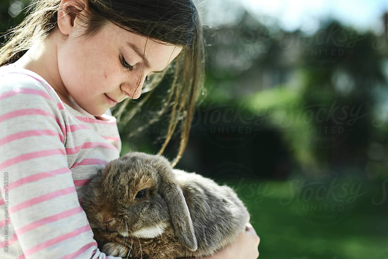 Girl holding a rabbit by Kirstin Mckee for Stocksy United