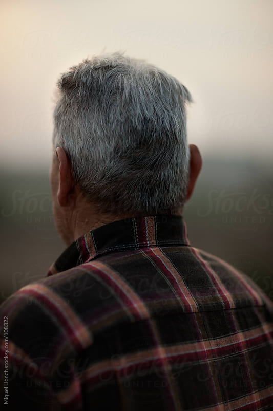 Portrait of an old man looking back with white hair and brown shirt by Miquel Llonch for Stocksy United