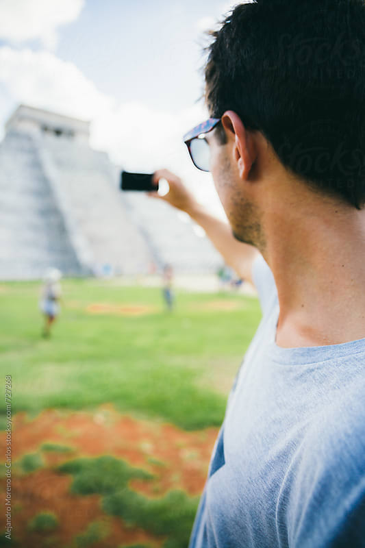 Young tourist man taking a photo with his phone to Kukulkan pyramid in Chichen Itza, Mexico by Alejandro Moreno de Carlos for Stocksy United