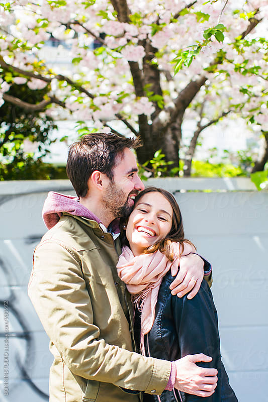 Happy lovers in front of a cherry tree. by BONNINSTUDIO for Stocksy United