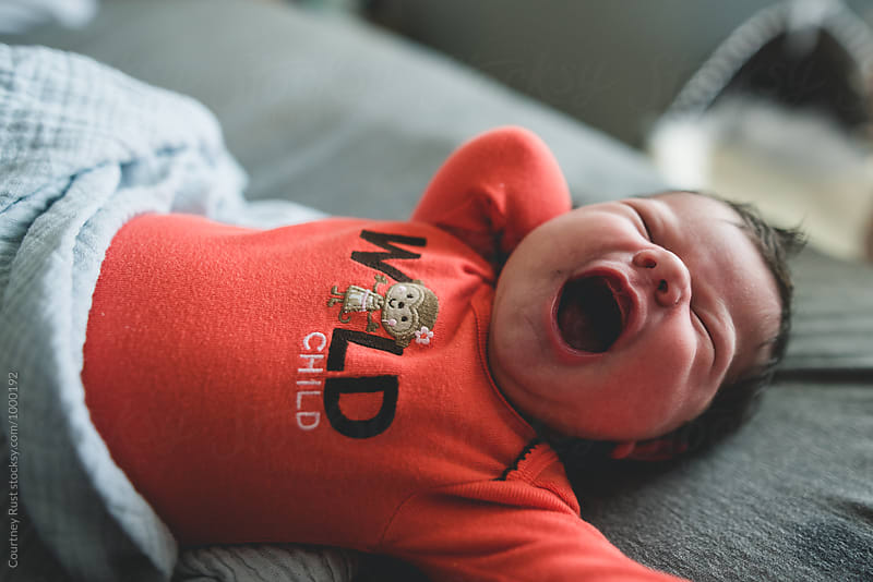 yawning newborn stretching in bed by Courtney Rust for Stocksy United