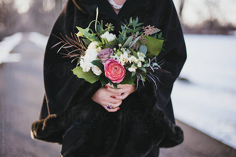 Woman in black cloak holding bouquet of flowers at sunset in winter by Daring Wanderer for Stocksy United