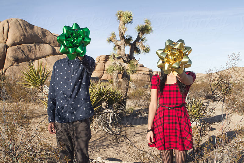 Couple Holding Oversized Gift Bows Over Faces by MEGHAN PINSONNEAULT for Stocksy United