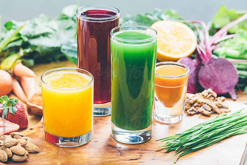 Colorful juices with an assortment of raw ingredients by Lior + Lone for Stocksy United